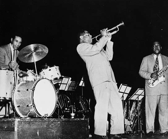 Charlie Parker watches Dizzy Gillespie play with Max Roach, drums