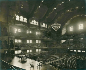 The elegant interior of Massey Hall in 1911, with an enormous chandelier and light pouring in through the windows.